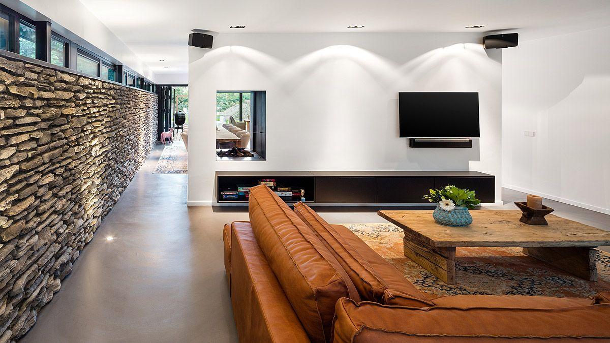 Natuurstenen wand in woonkamer. Ontwerp moderne woning door BNLA Architecten
